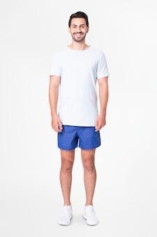 Mężczyzna w białej koszulce i niebieskich szortach z pełnym designem przestrzeni