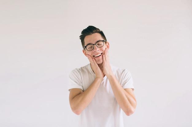 Mężczyzna w białej koszulce i szkłach z dużym uśmiechem odizolowywającym na bielu. bardzo miły student ma dobry humor