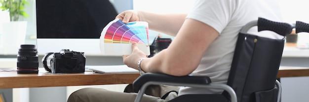 Mężczyzna w białej koszulce i zielonych spodniach siedzi na wózku inwalidzkim i trzyma w dłoni wielokolorową paletę. na stole znajduje się monitor, kamera, obiektyw i klawiatura.