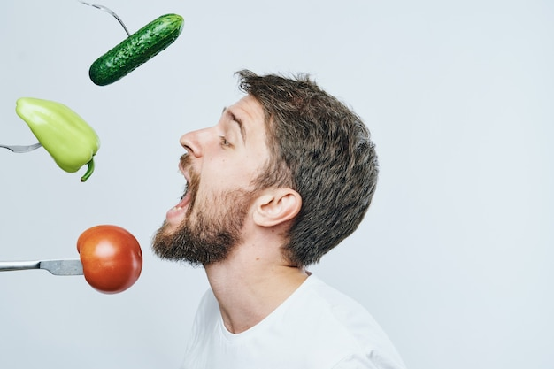 Mężczyzna w białej koszulce je warzywa