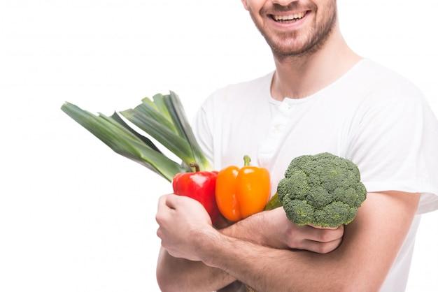 Mężczyzna w białej koszulce przytula warzywa.