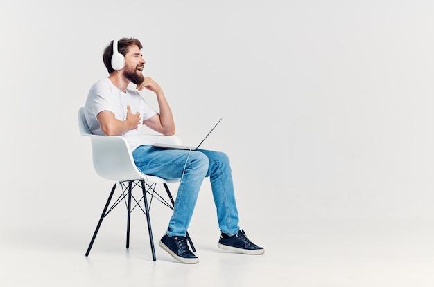 Mężczyzna w białej koszulce siedzący na krześle z laptopem w słuchawkach