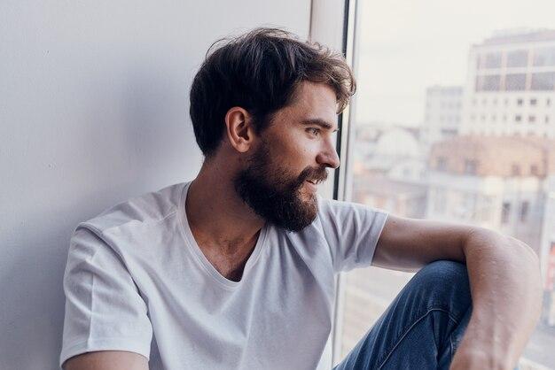 Mężczyzna w białej koszulce siedzący na parapecie w słuchawkach w komunikacji słuchawkowej