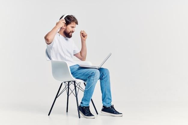 Mężczyzna w białej koszulce siedzi na krześle z laptopem w słuchawkach. zdjęcie wysokiej jakości