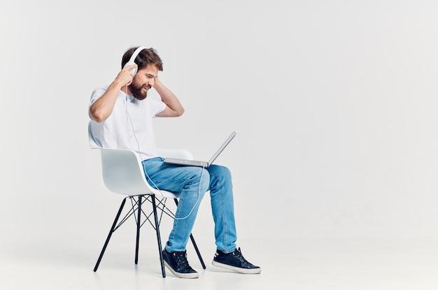 Mężczyzna w białej koszulce słuchający muzyki na słuchawkach odpoczywa