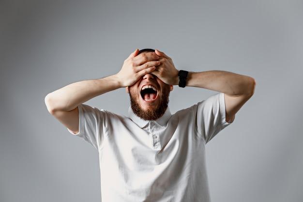 Mężczyzna w białej koszulce, śmiejąc się i zamykając oczy dłońmi na szaro.