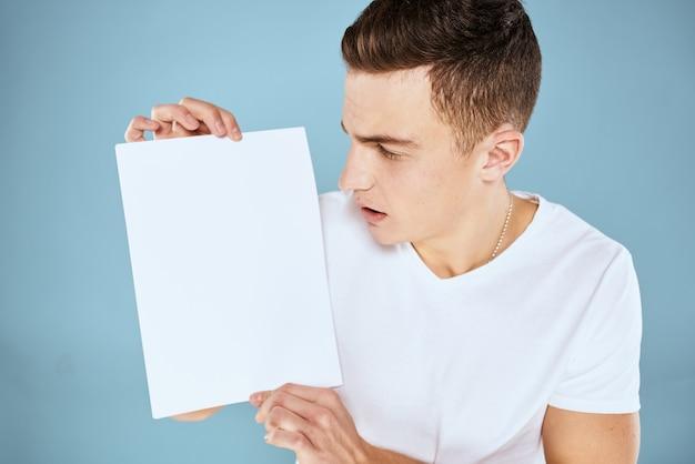 Mężczyzna w białej koszulce trzyma arkusz papieru kopia przestrzeń