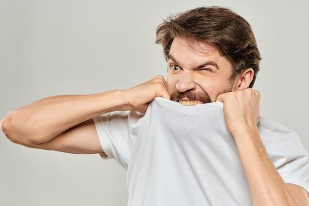 Mężczyzna w białej koszulce wyrażenia gest rękami przyciętymi widok jasnym tle