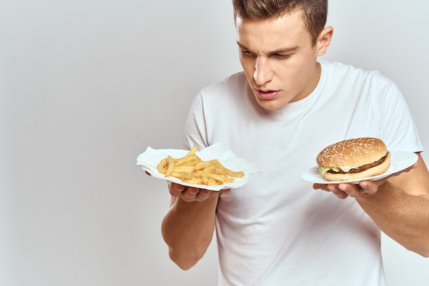 Mężczyzna w białej koszulce z burgerami fast food w rękach