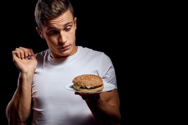 Mężczyzna w białej koszulce z fast foodem w rękach