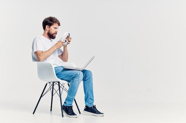 Mężczyzna w białej koszulce z laptopem w stylu życia słuchawek