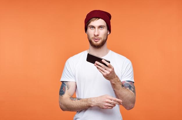 Mężczyzna w białej koszulce z telefonem w dłoniach na pomarańczowym tle technologii komunikacyjnej