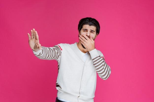 Mężczyzna w białej koszuli coś zatrzymuje lub zapobiega.