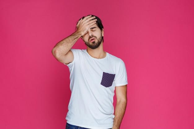 Mężczyzna w białej koszuli czuje się senny i zamyka oczy.