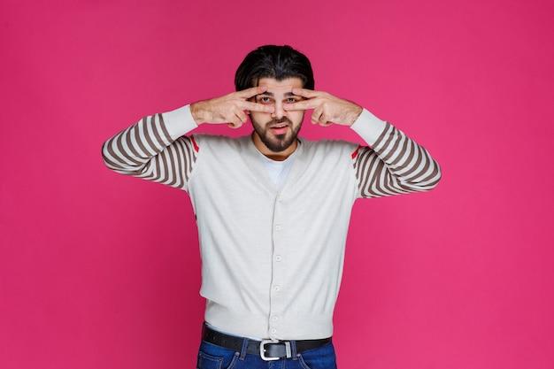 Mężczyzna w białej koszuli czyniąc znak ręką pokoju i wysyłając wiadomość.
