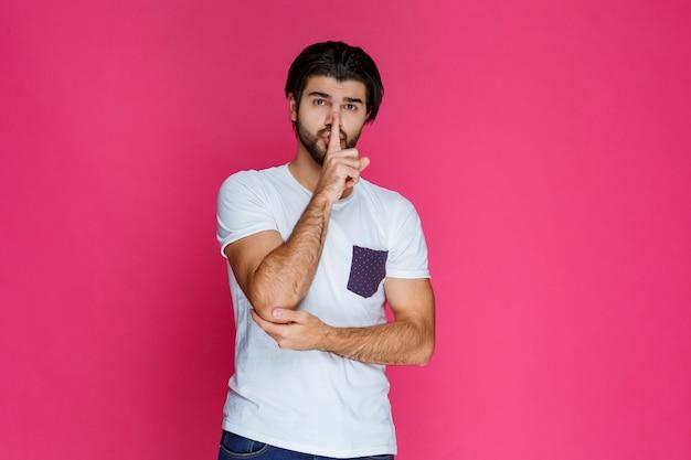 Mężczyzna w białej koszuli daje znak, żeby milczeć i przestać mówić.