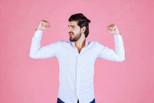 Mężczyzna w białej koszuli demonstrujący mięśnie ramion.
