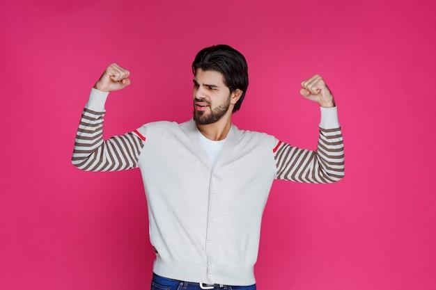 Mężczyzna w białej koszuli demonstrujący siłę i mięśnie ramion.