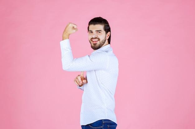 Mężczyzna w białej koszuli demonstruje mięśnie ramion.