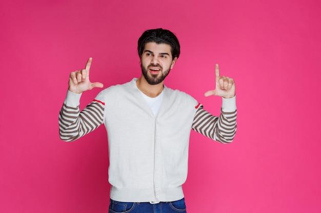Mężczyzna w białej koszuli dokonywanie brecket znak ręką.