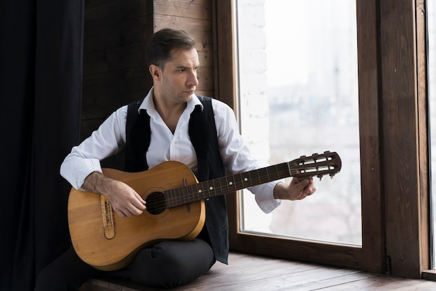 Mężczyzna w białej koszuli, gra na gitarze w swoim domu