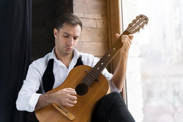 Mężczyzna w białej koszuli, gra na gitarze