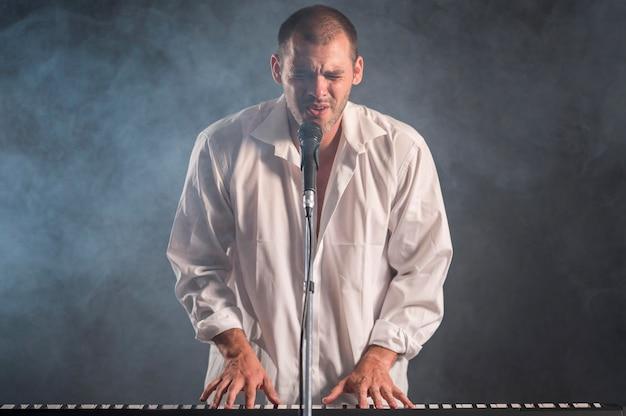 Mężczyzna w białej koszuli gra na klawiszach i śpiewa efekt dymu