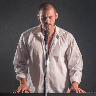 Mężczyzna w białej koszuli gra na klawiszach i śpiewa