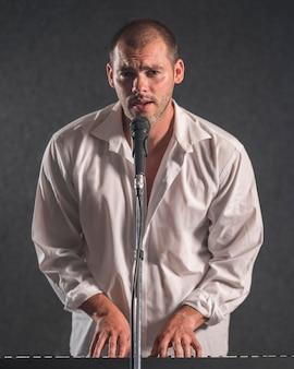 Mężczyzna w białej koszuli gra na pianinie cyfrowym i śpiewa