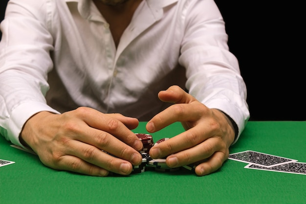 Mężczyzna w białej koszuli gra w pokera w biznesie hazardowym w kasynie. branża klubów nocnych. dużo pieniędzy. internetowy biznes pokerowy.