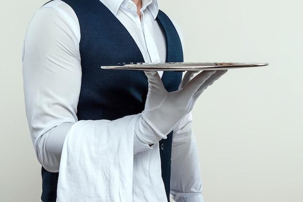 Mężczyzna w białej koszuli i białych rękawiczkach stoi bokiem ze srebrną tacą. koncepcja obsługi obsługującej klientów w restauracji.