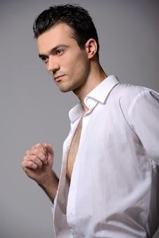 Mężczyzna w białej koszuli i krawacie stoi