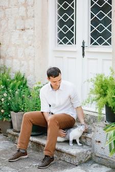 Mężczyzna w białej koszuli i spodniach siedzi na schodach w pobliżu pięknych białych drzwi i doniczek