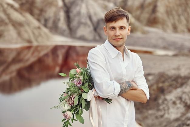 Mężczyzna w białej koszuli iz bukietem kwiatów w dłoniach czeka na dziewczynę na randce. portret mężczyzny z kwiatami na tle pięknych gór