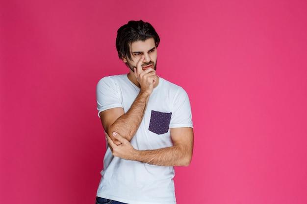 Mężczyzna w białej koszuli kładzie rękę na twarzy i myśli.