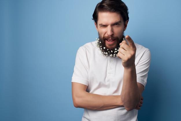 Mężczyzna w białej koszuli kwiaty w brodzie pielęgnacja włosów moda niebieskie tło