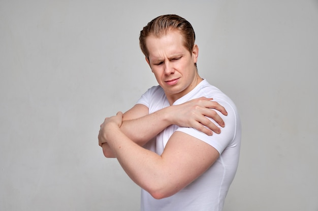 Mężczyzna w białej koszuli masuje ból ramienia. koncepcja masażu.