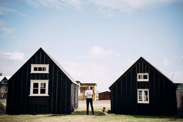 Mężczyzna w białej koszuli między dwoma drewnianymi czarnymi domami cel podróży islandia ślub
