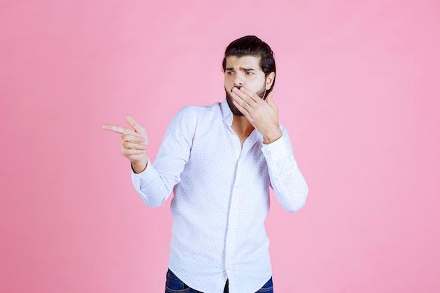 Mężczyzna w białej koszuli pokazujący lewą stronę z emocjami.