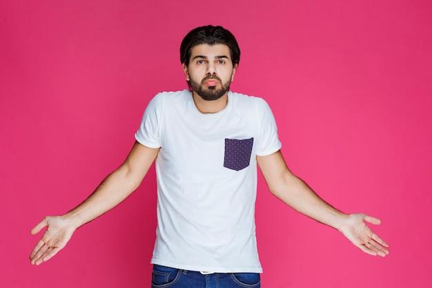 Mężczyzna w białej koszuli pokazujący, że nie ma pojęcia o temacie.