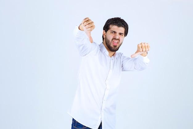 Mężczyzna w białej koszuli pokazujący znak kciuka w dół
