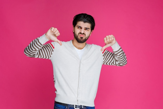 Mężczyzna w białej koszuli pokazuje kciuk w górę w dół znak.