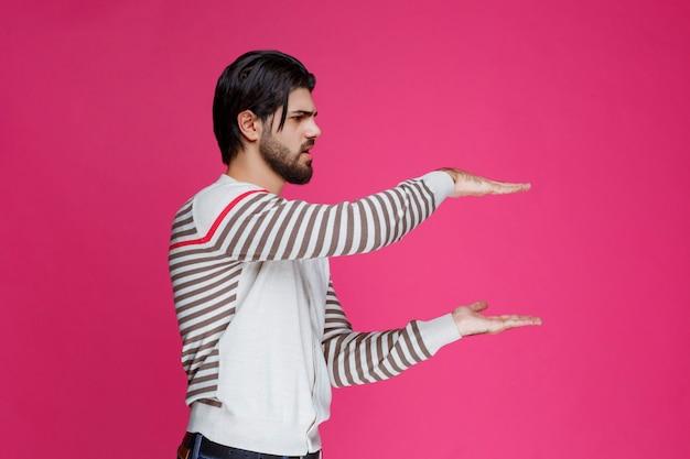 Mężczyzna w białej koszuli pokazuje wymiary paczki.
