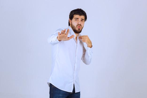 Mężczyzna w białej koszuli próbuje coś powstrzymać.