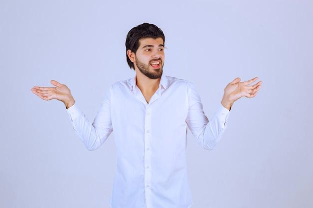 Mężczyzna w białej koszuli próbuje się wytłumaczyć.