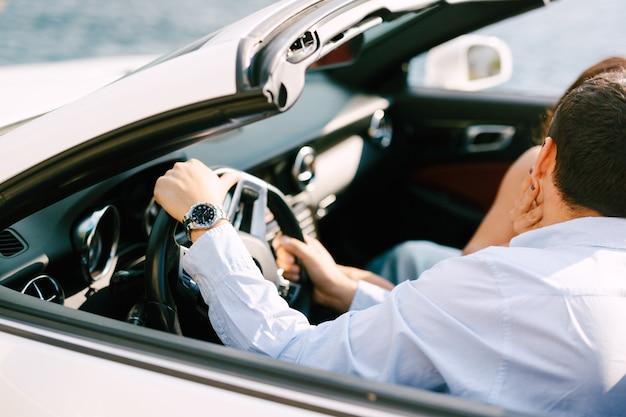 Mężczyzna w białej koszuli prowadzący kabriolet odwrócił się w stronę kobiety, która uniosła go dłonią pod brodę