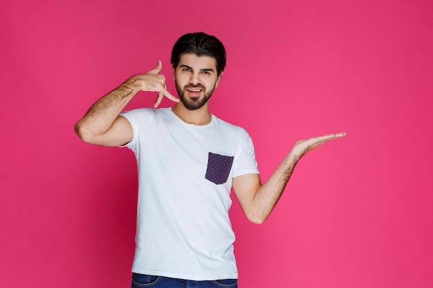 Mężczyzna w białej koszuli robi znak wywoławczy i prosi o połączenie