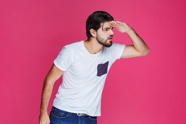 Mężczyzna w białej koszuli szuka czegoś w przyszłość.