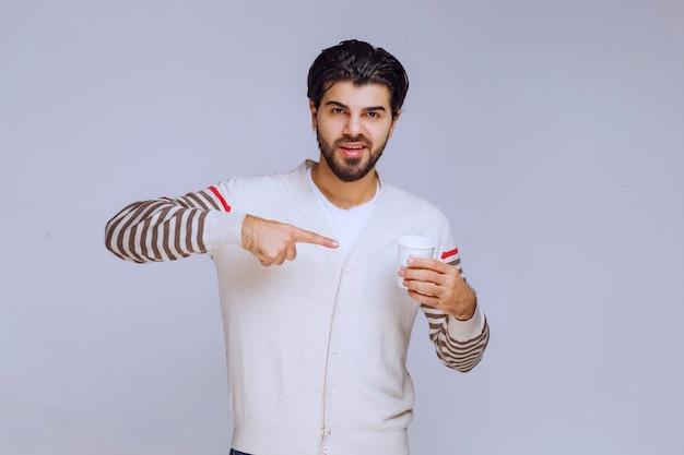 Mężczyzna w białej koszuli trzyma filiżankę kawy i wskazuje na to.