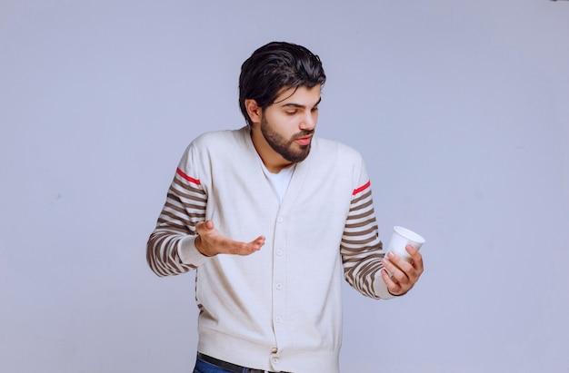 Mężczyzna w białej koszuli trzyma filiżankę kawy i wygląda zamyślony.